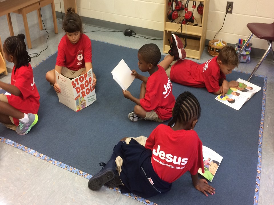 Group of five boys and girls wearing Jesus shirts and reading during After School Care at St. Paul Lutheran School Catonsville