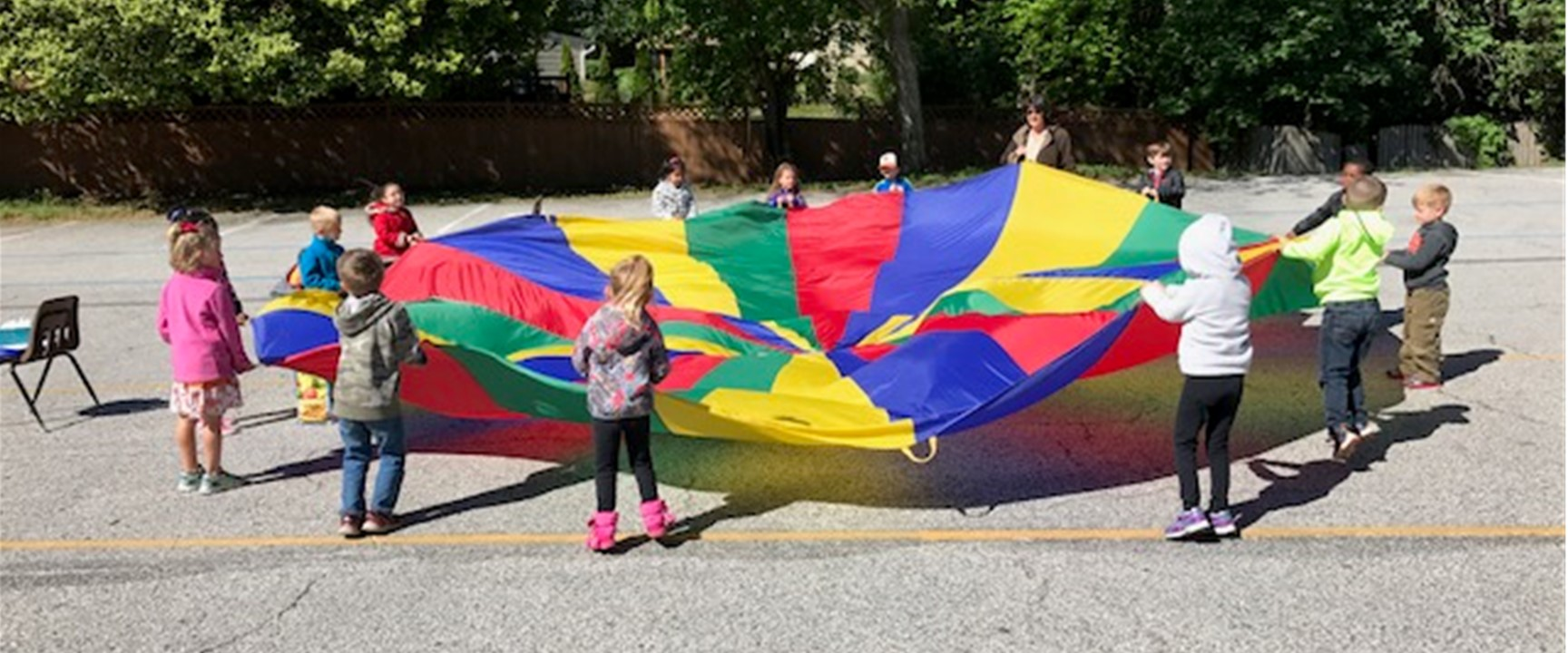 St Paul Lutheran School ECC Outdoor Learning Fun - Children in Circle with Colorful Parachute game
