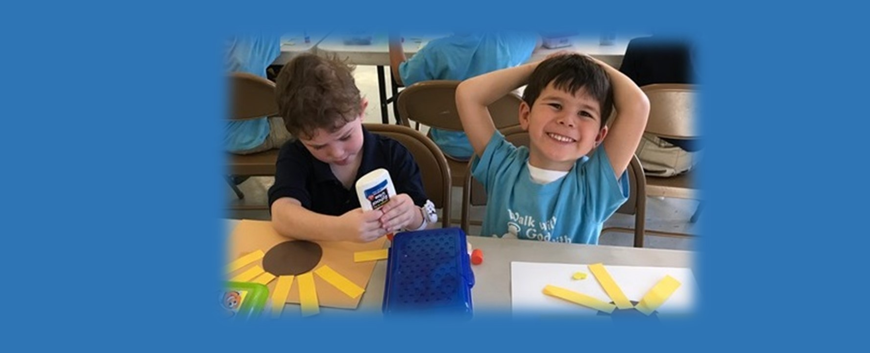 St Paul Lutheran School Catonsville Early Childhood Center student gluing strips of paper for a picture as another student smiles