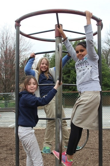 Three girls on playground climbing equipment at St Paul Lutheran School Catonsville