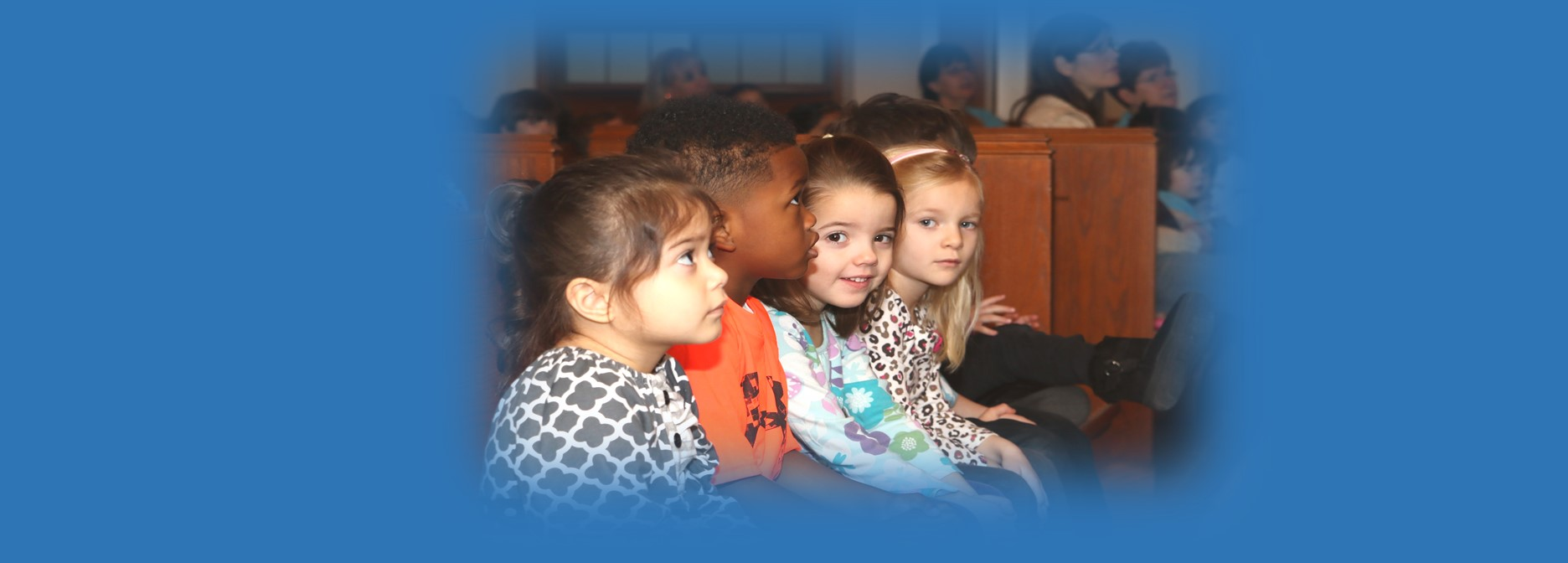 girl smiles at camera as st paul lutheran school early childhood center students listen during weekly chapel service