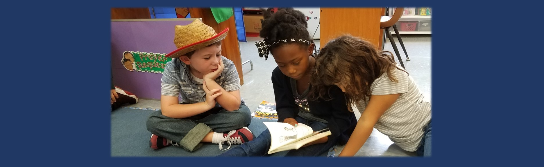 One boy and two girls reading together during Before School Care at St Paul Lutheran School Catonsville