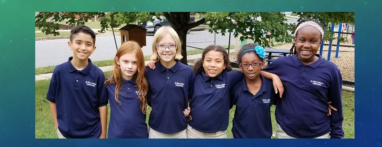 Smiling group of St Paul Lutheran School students wearing blue school uniform polo shirts